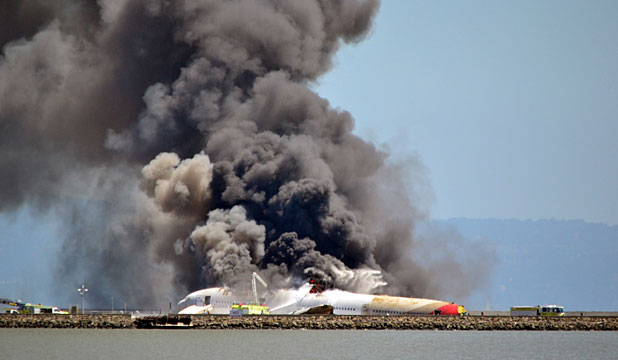 AIRPORT STALLS: Asiana Airlines flight 214 burns on the runway at San Francisco International Airport  after crash-landing on Saturday.
