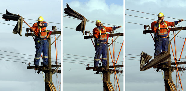 David Thomson, linesman with Tenix in Palmerston North, removes a sheet of corrugated iron blown onto the power lines.