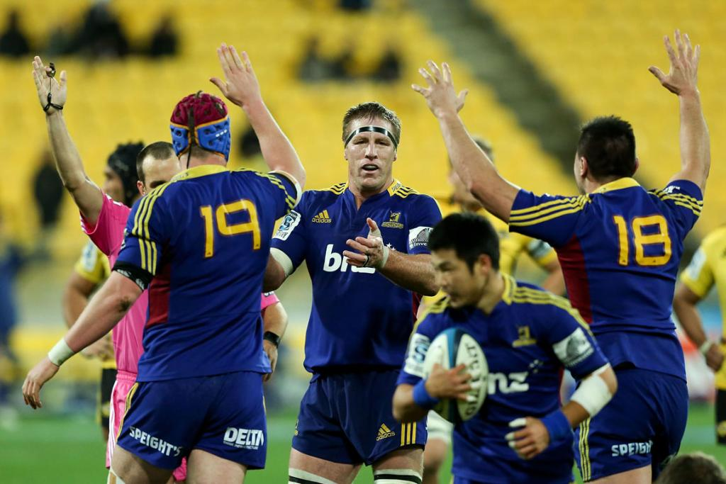 Joe Wheeler, Brad Thorn and Jake Pringatai of the Highlanders celebrate at the final whistle after their game with the Hurricanes.