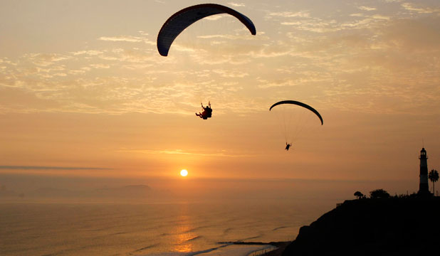 A FINE BASE: Paragliding instructors fly with tourists at an ocean-front in the neighbourhood of Miraflores in Lima.