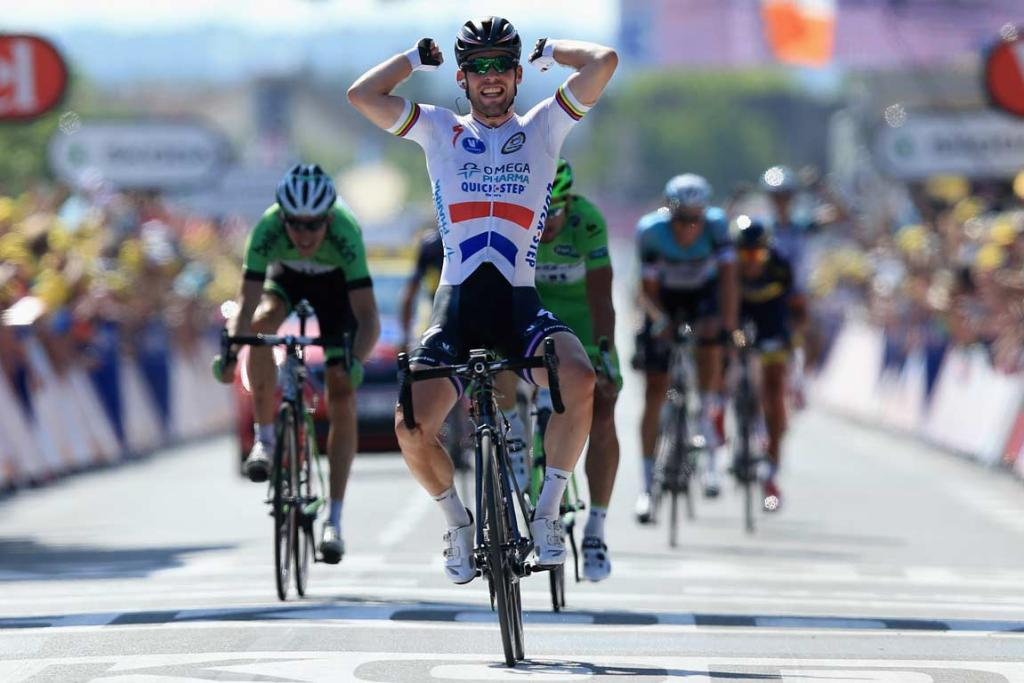 Mark Cavendish of Omega Pharmac-Quick Step raises his arms as he crosses the line to win stage 13.