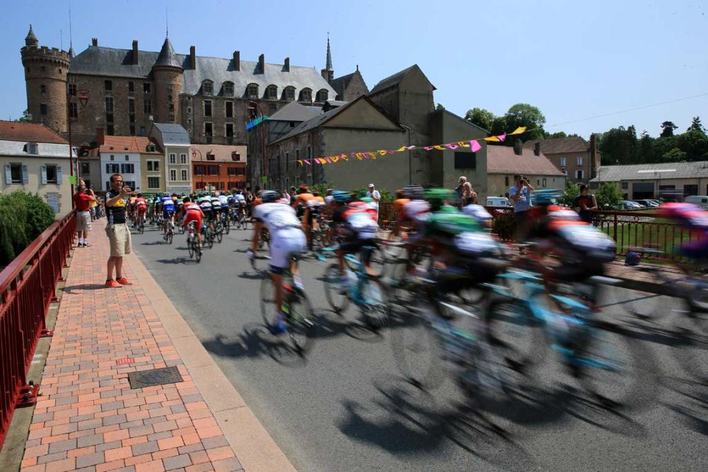 The Tour de France peloton arrive at a village during stage 14.
