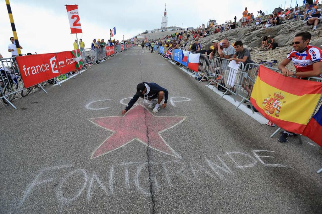 A spectator draws on the road during a mountainous stage.