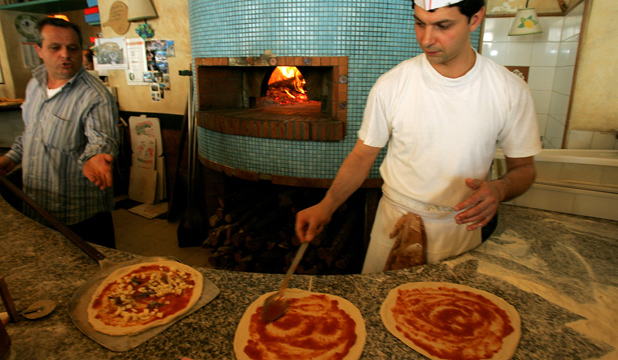 PIZZA PURISTS: Gennaro spreads tomato sauce on pizza bases as he prepares lunch at a traditional pizzeria