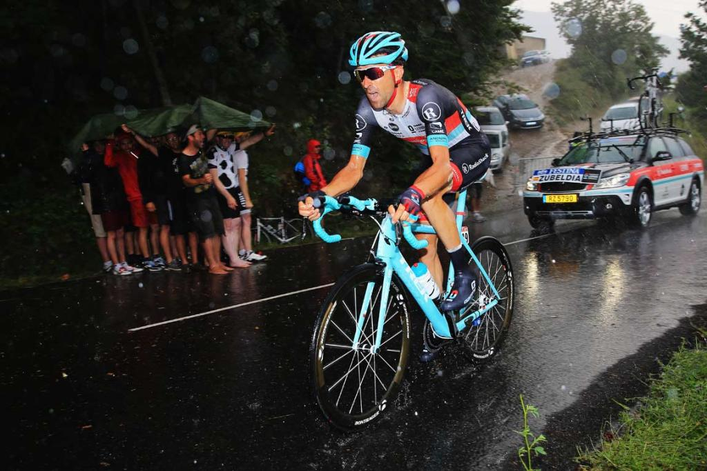 Haimar Zubeldia makes his way up a climb as heavy rain falls.
