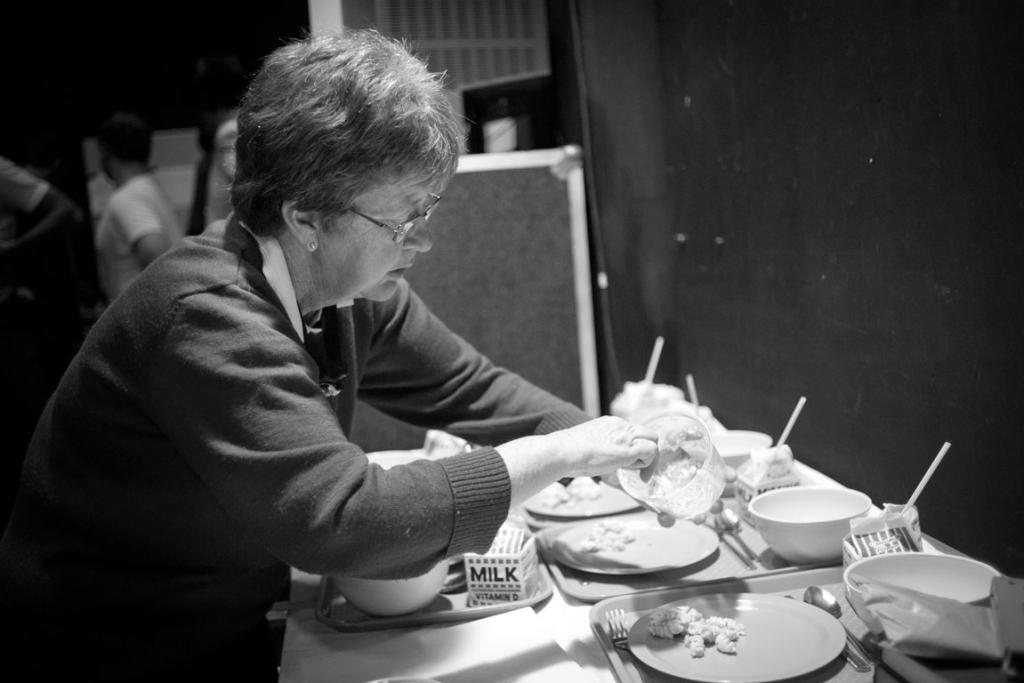Props manager Julia Adams fills plates with coleslaw and creamed rice for the cast to use onstage.