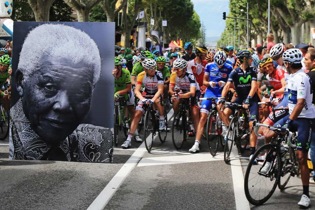 Tour de France riders wait behind a large picture of former South African president Nelson Mandela on his 95th birthday.