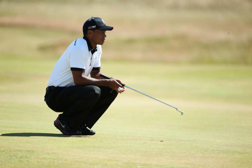 Tiger Woods lines up a putt early in his first round at Muirfield.