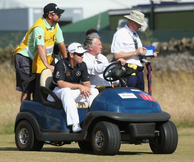 Louis Oosthuizen is taken from the course on a golf cart after withdrawing.