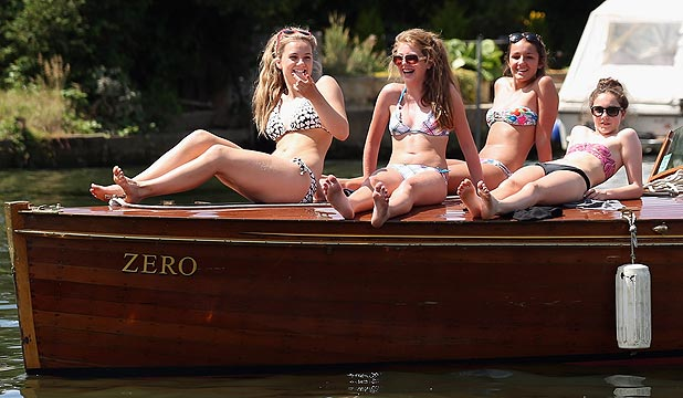 Women sunbathe on the front of a boat on the River Thames as they enjoy the hot weather in London.