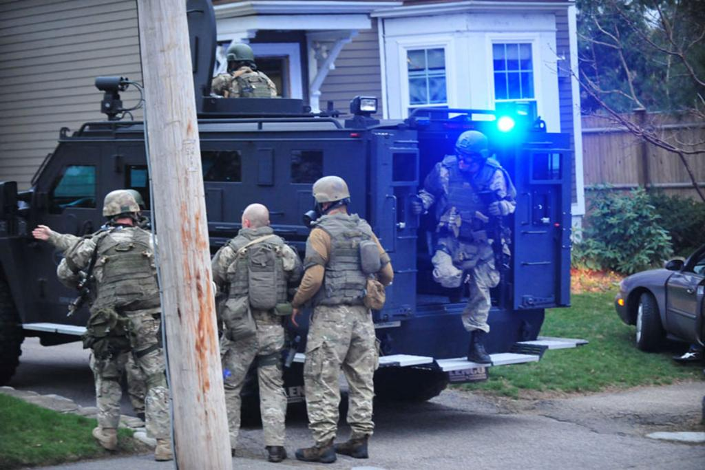 Police teams swoop on the suburban Boston house where the suspect was hiding.