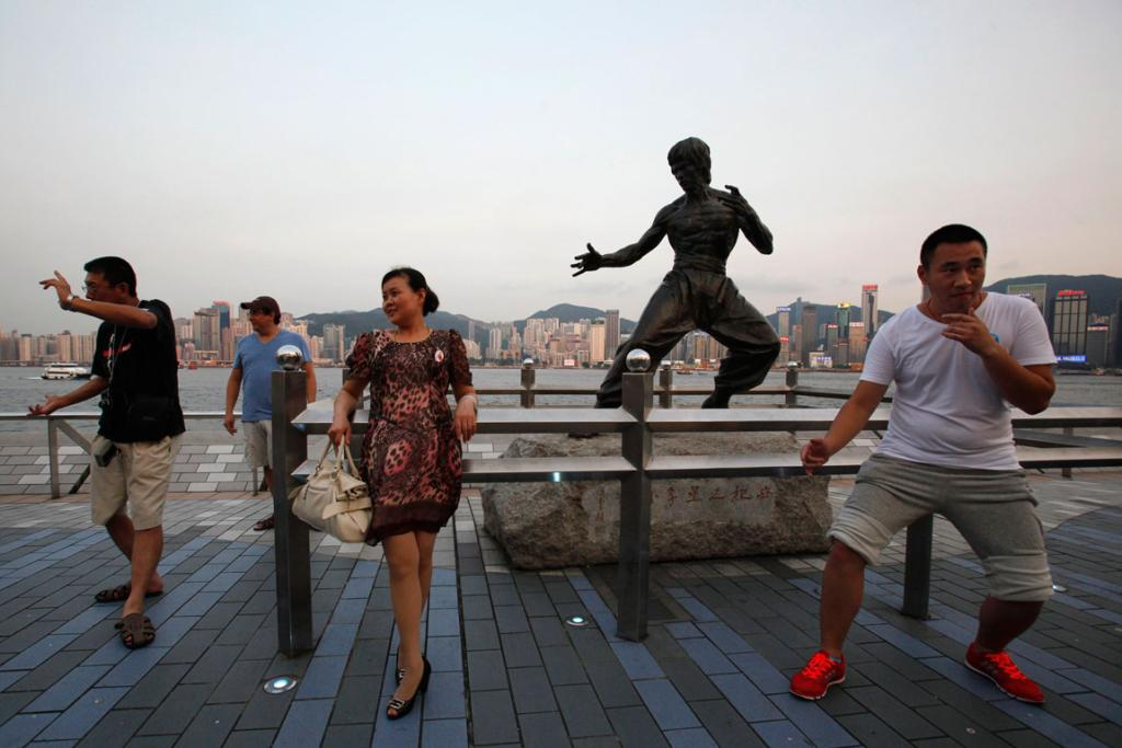 Tourists pose in front of a bronze statue of the late kung fu legend Bruce Lee on the waterfront facing Hong Kong island.
