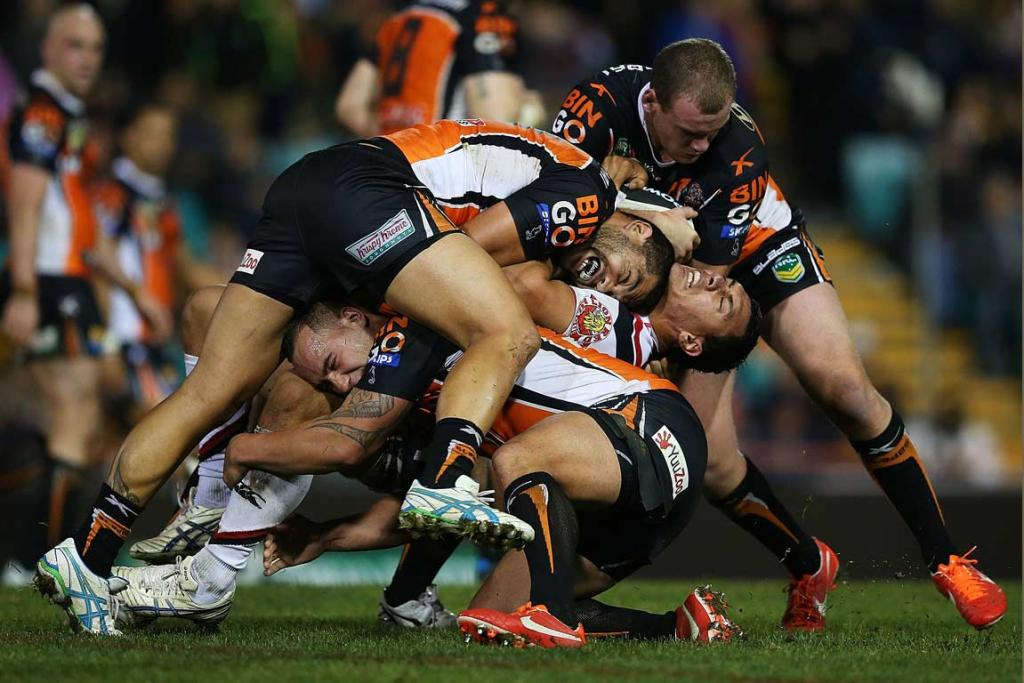 Warriors forward Elijah Taylor is bent back in the tackle of three Wests Tigers players.
