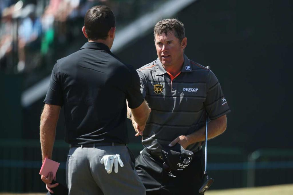 Lee Westwood shakes hands with Charl Schwartzel after the completion of their second round.