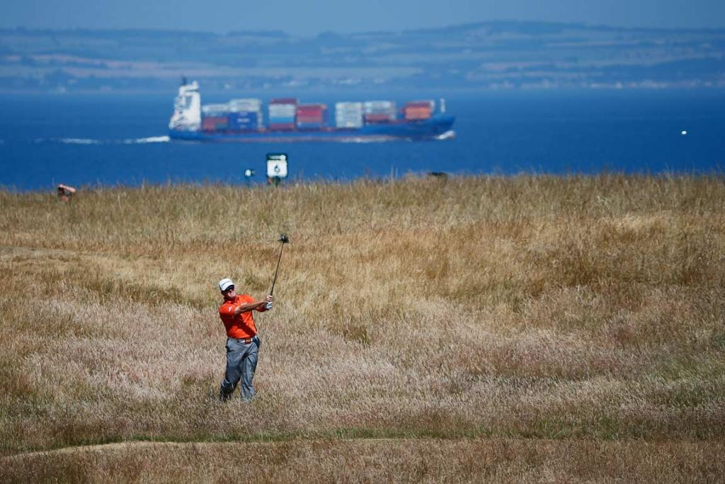 DA Points hacks out of the long grass as a freighter sails by behind him.