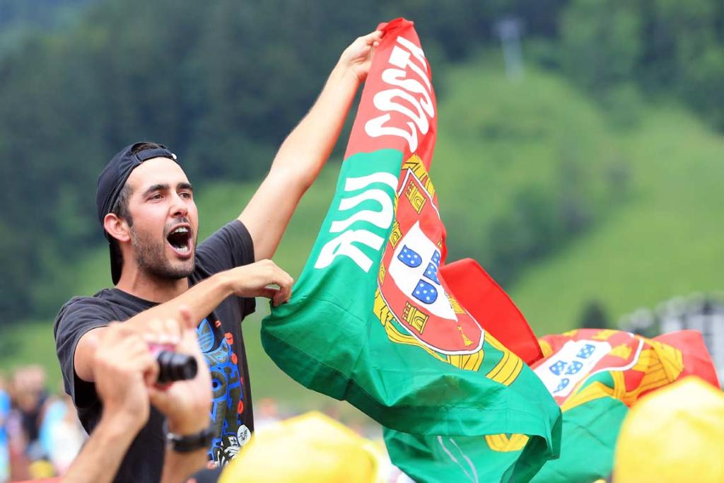 A spectator holds a Portugal flag with 'Rui Costa' written on it.