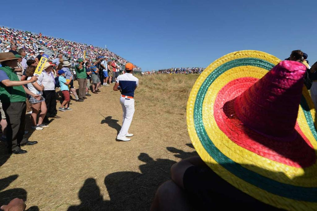 Rafael Cabrera-Bello plays from off the fairway in front of a sombrero-wearing spectator.