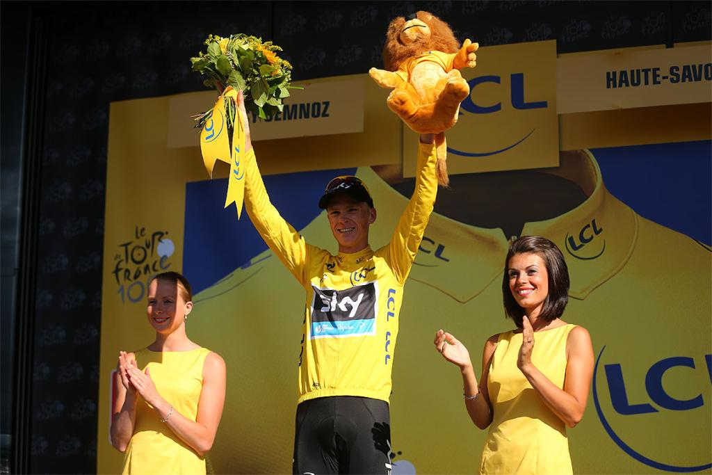 Chris Froome celebrates on the podium as he secures the leader's yellow jersey after stage 20.