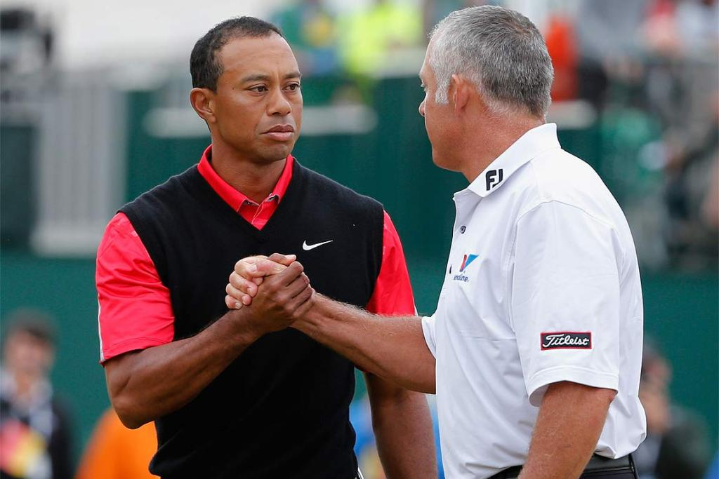 Tiger Woods shakes hands with his former caddie Steve Williams, who now works with Adam Scott.