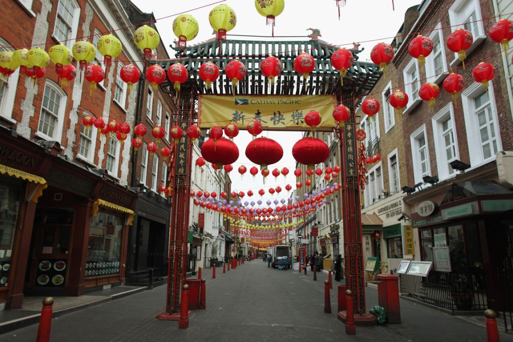 Chinese lanterns are strung in front of a Chinese arch on Gerrard Street in Chinatown, London.