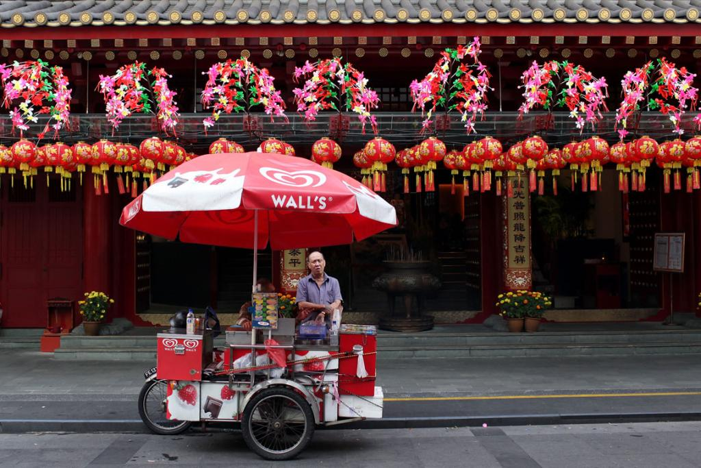 A street vendor waits for customers outside a decorated temple in Chinatown in Singapore.