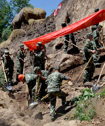 Paramilitary policemen search for victims after a large earthquake hit China's Minxian county