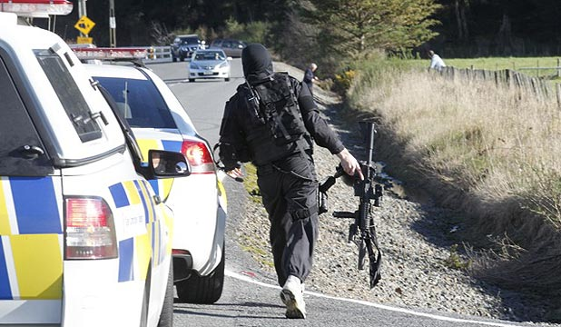 LOCKDOWN: An armed police officer at the scene of an AOS callout at Whitemans Valley, Upper Hutt.