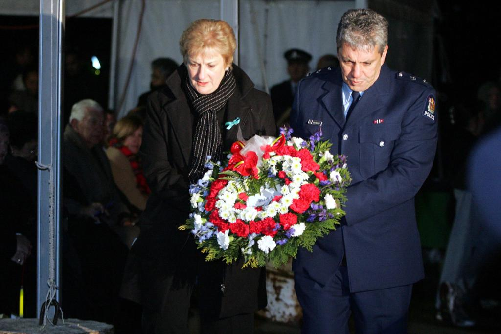 Minister Annette King and Superintendent Steve Shortland from the Manukau Police carry a wreath to remember murder victim Claire Hills who was killed on Mangere mountain several years ago.