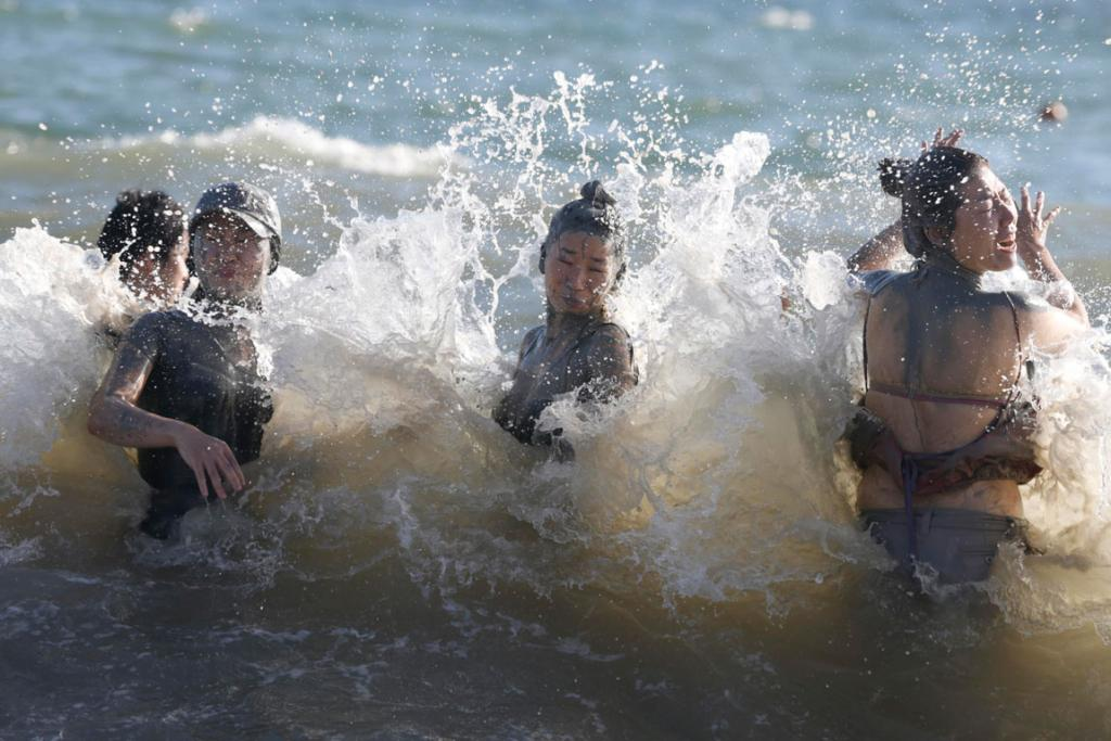 Tourists wash off the mud at Daecheon beach after the mud festival.
