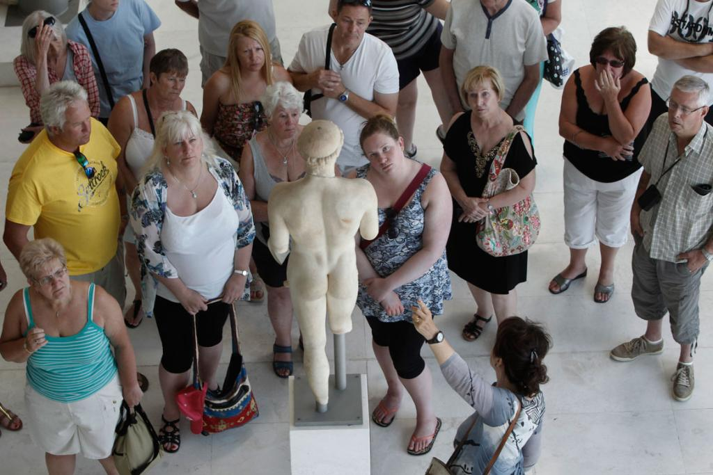 Tourists admire an ancient statue in the hall of the archaic period at the Athens Acropolis.