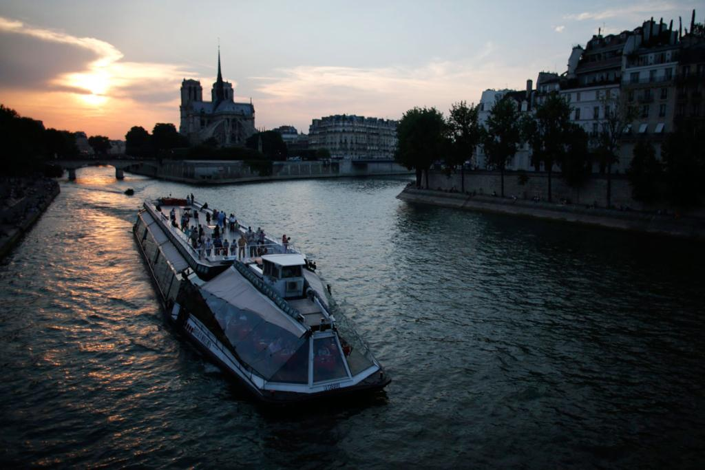 A tourist boat travels along the River Seine as the sun sets near the Notre Dame Cathedral in Paris.