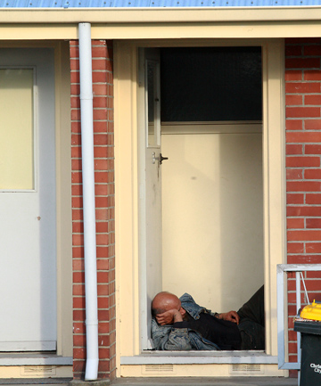 SUN SPOT: A resident sleeps in the doorway of a Macgibbon Place housing unit.