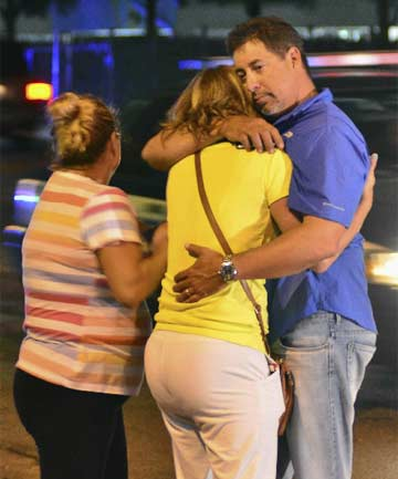APARTMENT RAMPAGE: A woman is consoled after a shooting in a Miami suburb that left seven people dead.
