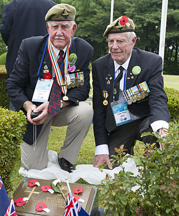CLEAR MEMORIES: Clarence Maskill and Charles Sibun lay poppies on a New Zealand grave  in the United Nations Military Cemetery Korea in Busan, South Korea.