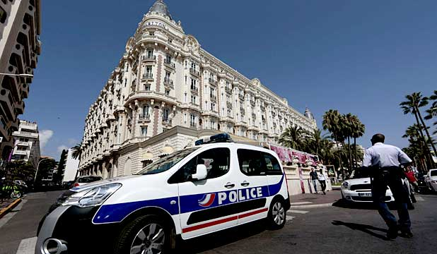 A police car parked outside the Carlton Hotel in Cannes where several million euros worth of jewelry and watches were stolen.