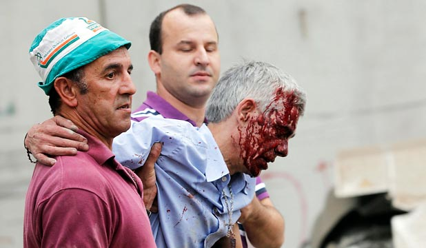 AFTER THE CRASH: Driver Francisco Jose Garzon Amo is carried from the crash scene by Evaristo Iglesias, in pink, and another man. Iglesias said Garzon commented that he tried to stop the train but couldn't.
