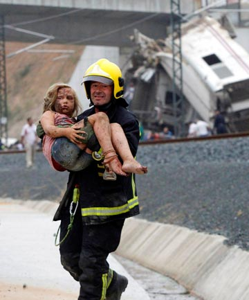 FREED: A rescue worker carries a young victim from the crash scene during the aftermath.