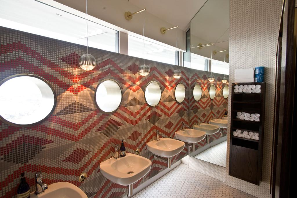 Mosaic tiles, ship-style windows and ornate lights give the bathroom a 1930s vibe.