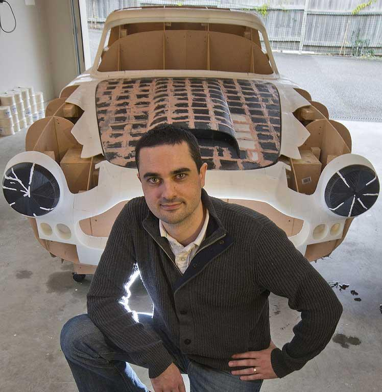 Ivan Sentch kneels in front of the mould for an Aston Martin DB4 replica which he is building with a 3D printer in his garage on Auckland's North Shore.