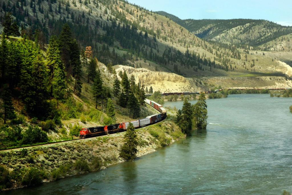 A freight train making its way through the Rockies is seen from the Rocky Mountaineer train.