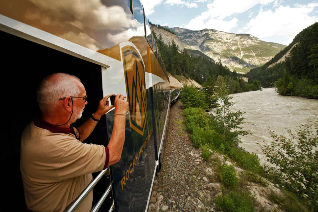 Patrick Sutcliffe takes photos from an open-air vestibule on the Rocky Mountaineer train.