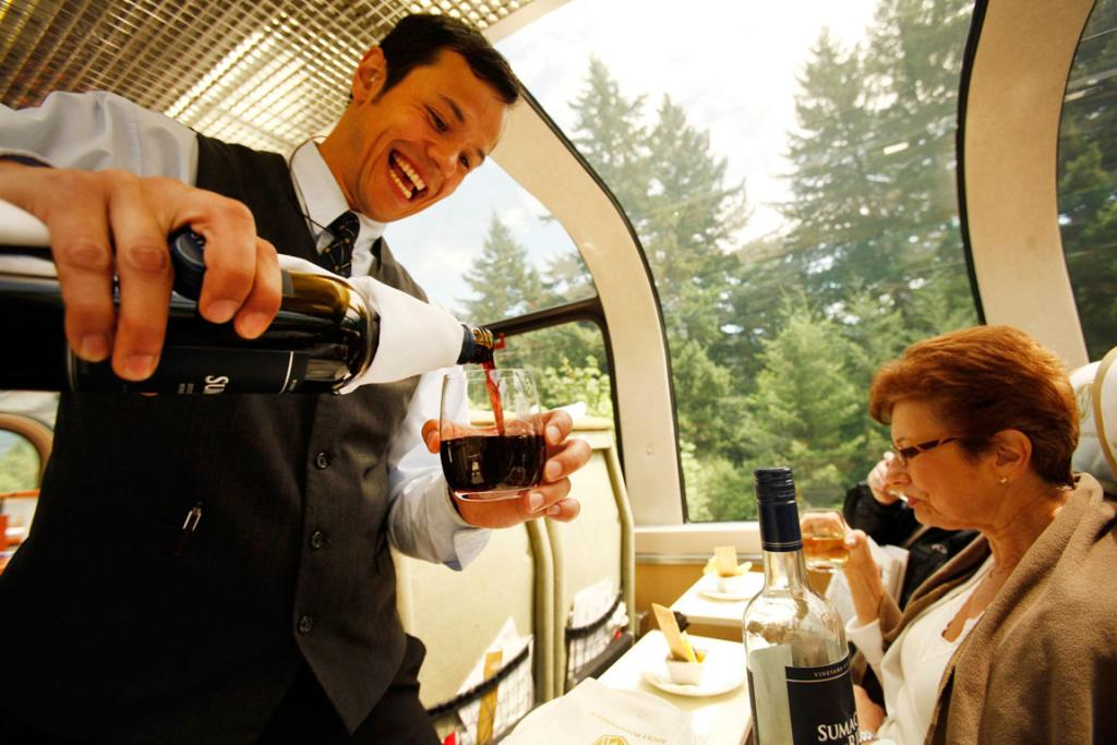 Carlo Myles pours wine for passenger Susan Kaplan on the Rocky Mountaineer train on a trip.