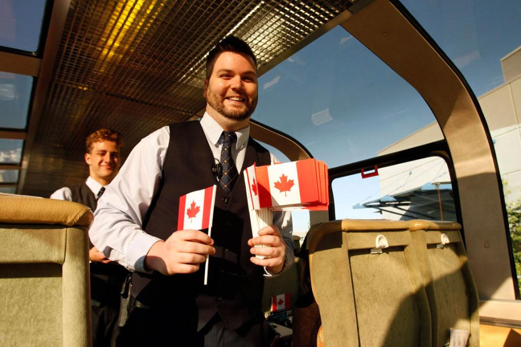 Charlie Millar, guest services manager, passes out Canadian flags to passengers.