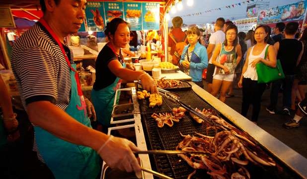 FOOD STREET: Seng Sivilay, left, and Spina Huang prepare food at their BBQ Squid stand in the Asia market in Richmond near Vancouver, British Columbia, Canada.