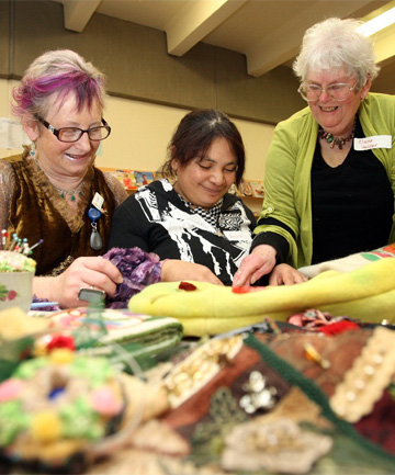 Invercargill Library research librarian Vonnie Crawford, left, and helper Elaine Little, right, show Aroha Adam how to make a button brooch at the Crafternoon Tea held  at the library.