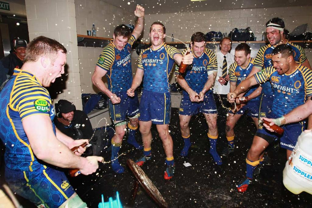 Otago players spray some of the sponsor's product in the changing room.