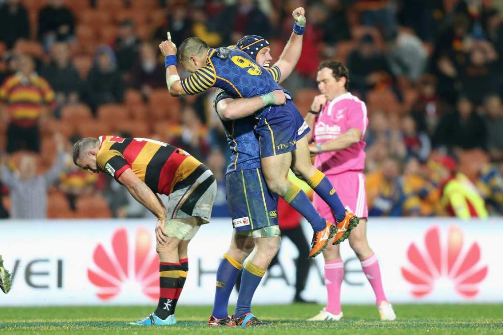 Halfback Fumiaki Tanaka jumps into the arms of Charlie O'Connell at the final whistle.