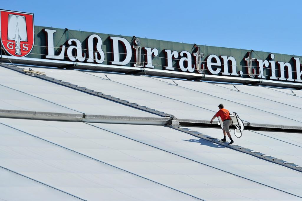 Workers carries giant letters of the illuminated advertising of the Spaten beer tent during the preparation for the 2013 Oktoberfest beer festival.