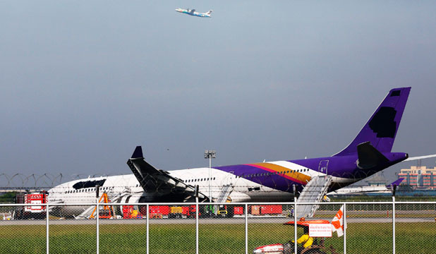 NOSE DOWN: An airplane takes off in the distance as airport staff work around a Thai Airways plane that skidded off the runaway while landing at Bangkok's Suvarnabhumi Airport