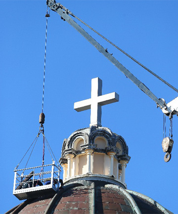 Workmen replace a copper panel on top of St Mary's basilica, in Invercargill.